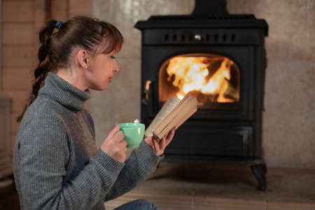 Pretty long hair brunette girl with pigtail in gray sweater reading by fireplace with cup in her hand in cozy darkened room winter autumn evening. Loneliness Concept. concept of serenity