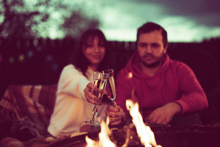 couple of lovers toasting with champagne glasses in their hands on background of fire at romantic party by bonfire. Loving man and woman relaxing near campfire in open air, Inspiration for wedding