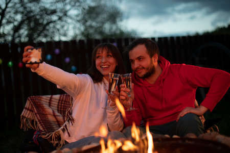 couple of lovers having fun making selfies with smartphone holding champagne glasses in hands at warm romantic party by bonfire. Great warm evening On Vacation Outdoors. togetherness concept Reklamní fotografie