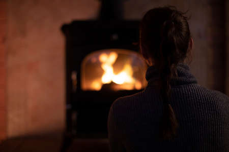 back view of Pretty long hair brunette lone girl with pigtail in gray sweater looking at fireplace in cozy darkened room winter autumn evening. Loneliness Concept. concept of serenity