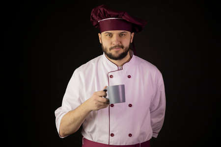 smiling young bearded male chef cook or baker man in uniform holding cap coffee or tea in his hand looking at camera isolated on black. copy space. novice cooker. keep calm concept. beginner chef