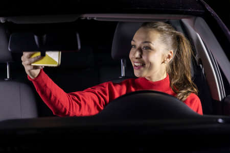 Happy woman in car at night stopped parked and makes video calls to family. Smiling female driver sitting inside car makes selfie. Concept: Safe journey, mobile and internet connection with relatives