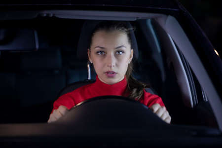 Woman is driving car at night. Serious female driver sitting inside car looks confused forward to the road clings tight to wheel on night trip. Concept: nerves and transportation. Safe journey