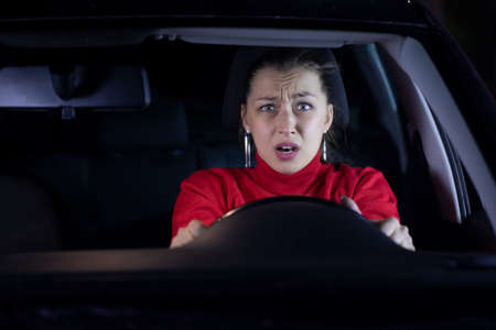 Frightened female driver has car accident on road. Young woman driving car shocked about to have traffic accident, windshield view. People, driving, problems with transport, car crash, people emotions