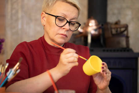 Portrait of female artist painting on yellow clay pot in art home studio workspace. Handmade pot, DIY, creative pottery workshop, decoration painting utensils, creative hobby concept