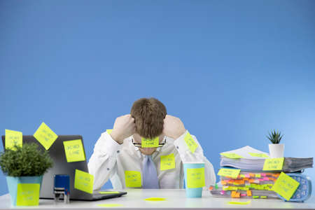 Frustrated manager does not cope with deadlines at work. A lot of work, paperwork. Everything is glued with stickers on the workplace. Isolated on a blue background.