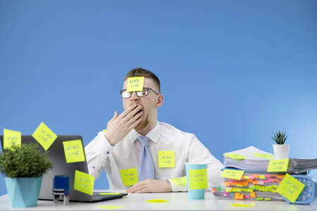 Manager does not cope with the work and yawns, does not have time to do the work on time. Deadline concept. A lot of paperwork. Everything is glued with stickers on the workplace.