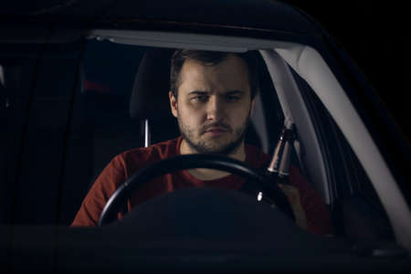 A drunk driver drives a car holding a bottle of beer in his hand. Drunk driving on highways at night. Dangerous driving, breaking the law. Drinking alcohol while driving. Alcohol addiction concept.