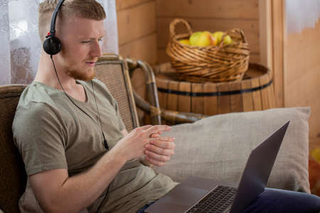 Handsome male freelancer communicating in social network and working remotely from home. Work in the living room. Side view man sitting at wooden table and participates in video conferencing