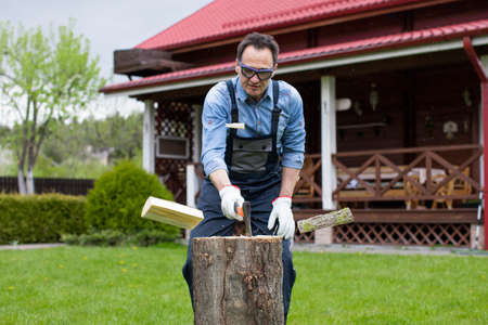 Adult man in jeans shirt and overalls chopping wood with axe in rural. Collecting firewood. Life in a country private house. Mens work. Flying pieces of wood and sawdust.