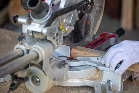 A carpenter cuts a timber beam with a circular saw. A closeup of hands in gloves. A sharp rotating disc that cuts through wood. Shavings and sawdust fly. Stockfoto