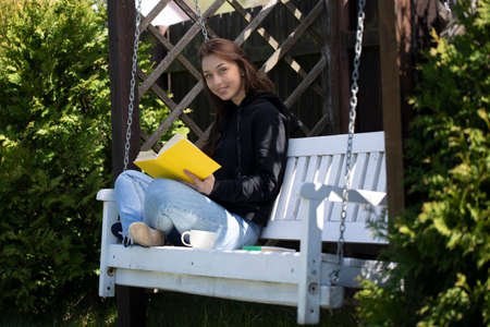Young beautiful woman sitting on wooden swing in backyard of country house, reading book outdoors, looks at camera with smile, nature background. Summer leisure, self education, study concept Stockfoto