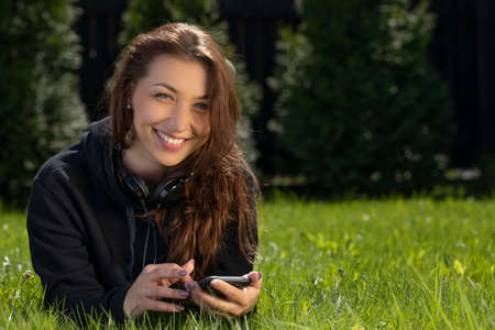 Woman lies with a phone on the grass in the garden near the house and broadly smiles. Relaxing on lawn concept. Outdoor recreation. Holidays in the village. Warm sunny summer day.