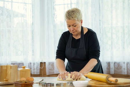 Caucasian housewife in a black apron kneads raw dough with her hands on the table with flour. Wooden kitchen interior. Homemade holiday cookies.