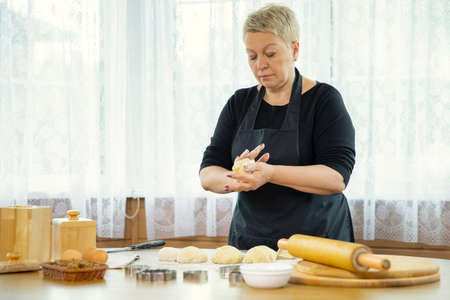 Caucasian housewife forms cakes from raw dough on a table sprinkled with flour. Cooking festive gingerbread cookies. Wooden kitchen interior. Stock fotó