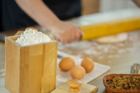 Wheat flour in wooden jar and eggs on oak kitchen table. Caucasian housewife rolls out the pizza dough with a rolling pin. Concept of home baking. Quarantine time.
