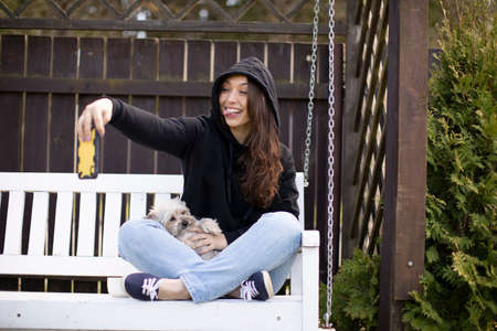 Beautiful woman in a hoodie makes selfie while sitting on a garden swing. Outdoor recreation. Holidays in village. Relaxing on garden. Warm sunny summer day.