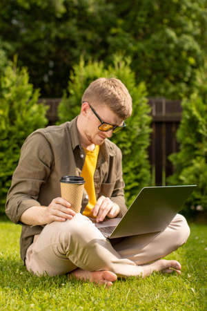 barefoot young man wearing yellow glasses sitting on grass with laptop and single-use cup of coffee. Young millennial male student searching information for homework using wifi connection outdoors