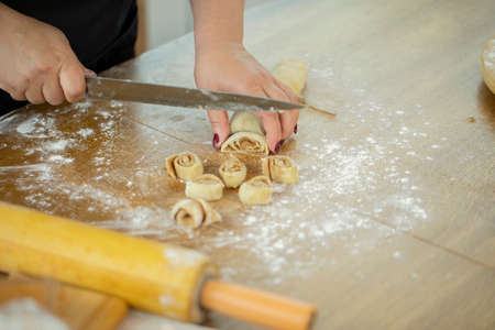 Caucasian housewife in an apron cuts a roll of dough with cinnamon with a knife. Wooden kitchen table. Close-up of hands of a happy housewife. Cooking festive cinnamon rolls.