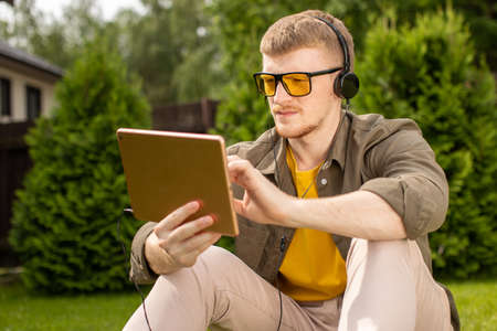 Smart handsome male student in headphones holds touchpad testing music learning application, young man siting on grass in park resting working on digital tablet. Distance study, training apps concept