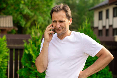 Happy middle aged man in casual clothes making phone call outdoors, handsome businessman talking on mobile phone with family, business colleagues. Communication, people, digital concept
