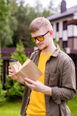 Handsome hipster guy resting in park with paper book and cup of tea, young businessman freelancer student reading outdoors. Summer, self education, study, training courses and programs concept Archivio Fotografico
