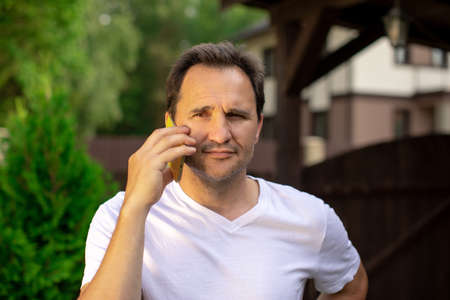 Closeup portrait view of one handsome unshaven pensive 40s man in white T-shirt speaking on mobile phone outdoor on blurred green natural background, horizontal picture. concept of equanimity