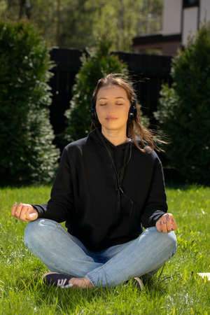 Woman meditates while sitting on green grass on lawn and listens to relaxing music. Rest on lawn concept. Relaxing on green grass. Outdoor recreation. Holidays in the village. Warm sunny summer day.
