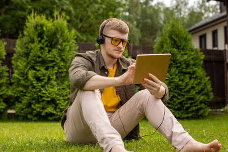Smart handsome male student in casual clothes and headphones holding tablet in hands watching webinar, listening podcast, young man siting on grass in park resting. Modern technologies concept