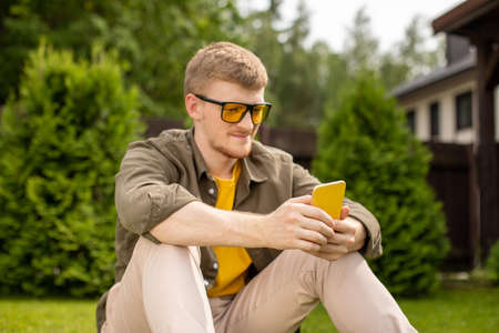 Young handsome man in casual wear resting on grass in park checking new app, texting message on smartphone, playing games on mobile phone. Focus on phone, copy space, summer, people, gadgets concept