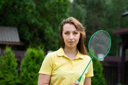 Attractive   woman standing with badminton racket in open air. sport brunette on green background. Active outdoor sports games. Outdoor workout Archivio Fotografico
