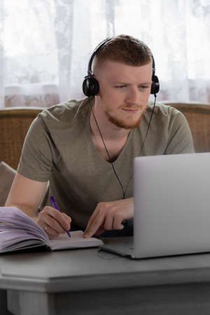 attractive thinking young man in headphones works with laptop, makes notes in diary in country wooden house on background of white curtain remote work concept online conference concept