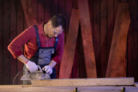 middle-aged male carpenter processes wooden workpiece with electric planer on workbench at cottage workshop. Carpentry work on wood. Working in country house.