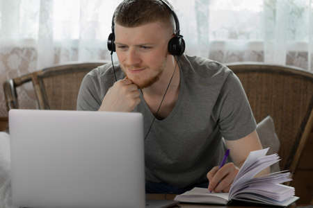attractive thinking young man in headphones works with laptop, communicates in social networks, makes notes in diary in country wooden house on background of white curtain online conference concept Archivio Fotografico