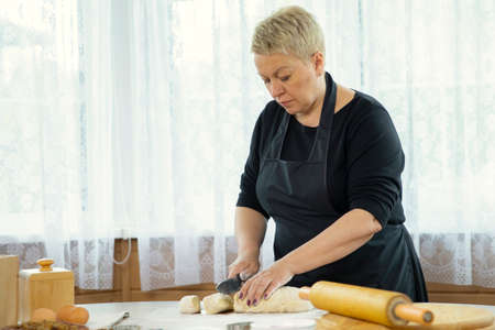 middle-aged woman wearing black apron making homemade cookies and pastry slices dough in kitchen �ookery class family traditions concept Homemade baking lesson concept. blogging concept Banque d'images