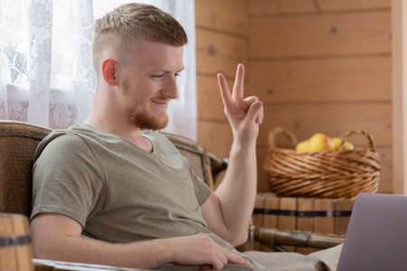 attractive young man works with laptop, communicates in social networks, gesturing V-sign, in country wooden house on background of basket of yellow apples and white curtain remote work concept Archivio Fotografico