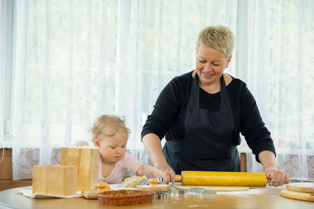 Grandma and granddaughter roll out dough on wooden table sprinkled with flour. family traditions concept. Togetherness Concept. Homemade baking lesson concept. videoblogging concept
