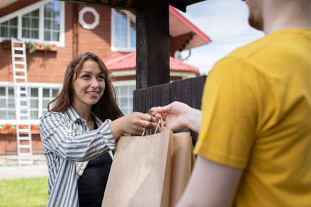 Smiling beautiful woman customer receiving order from delivery man in front of house, Fast delivery Online delivery service concept, delivery home, e-commerce, shipping, online shopping food order