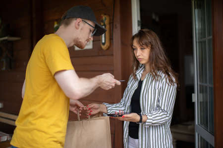 Delivery man in yellow uniform handing paper bags to beautiful young woman customer checking order in mobile app, express delivery, food delivery service, online shopping concept, e-commerce
