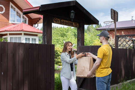 Beautiful woman customer receiving order from courier, Delivery man in yellow t-shirt handing paper bags to recipient in front of country house, delivery service concept, e-commerce, online shopping Archivio Fotografico