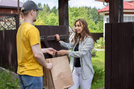 Young woman customer receiving order from courier, Delivery man in yellow t-shirt handing paper bags to recipient in front of country house, delivery service concept, e-commerce, online shopping Archivio Fotografico
