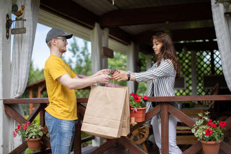 Delivery man handing paper bags to female recipient, beautiful young woman customer receiving order from courier at home, pays for order in cash, express delivery service, online shopping concept
