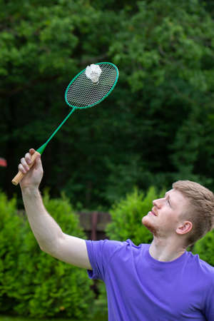 Young strong sport Caucasian man plays badminton with racquet and shuttlecock on green background. concept of amateur game of badminton, outdoor activities.