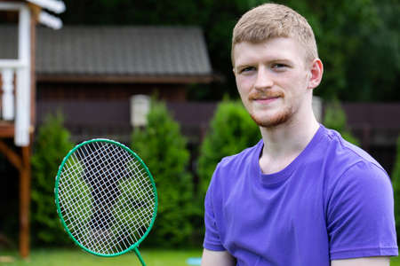 Young strong sport Caucasian man posing with badminton racket on green background. concept of amateur game of badminton, summertime outdoor activities Stock Photo