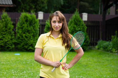Beautiful sexy woman posing with badminton racket in open air. brunette with badminton racket on green background. Active outdoor sports games. Outdoor workout. Archivio Fotografico