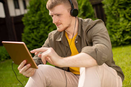 Handsome student in headphones with digital tablet listening podcast, testing learning application, young man siting on grass in park on sunny day resting. Modern technologies, multitasking concept Archivio Fotografico
