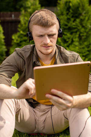 Close up confident man in headphones holding touchpad watching webinar, listening podcast, working on digital tablet. Modern technologies, online business, distance learning, training apps concept