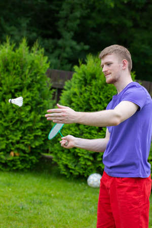 Young strong sport Caucasian man plays badminton with racquet and shuttlecock on green background. concept of amateur game of badminton on meadow, outdoor activities.