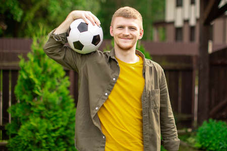 young caucasian man in everyday clothes carry soccer ball on his shoulder on green lawn of country house. amateur football invitation