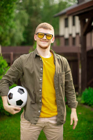 Portrait of young handsome man holding soccer ball smiling and looking at camera, Happy male football fan support sport team. People, person, amateur player, entertainment concept, bet on sports